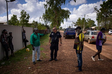 Paul Jones, sergeant at the Wadeye Police Station, talks with a group of Aboriginal elders as he walks around the Wadeye. In a town where very little traditional policing occurs (many of the cases are...