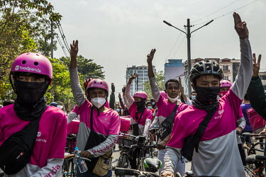 Food panda delivery cyclists hold up their hands displaying the three fingers pro-democracy gesture as they join as protestors who are marching in support for the NLD (National League for Democracy),...