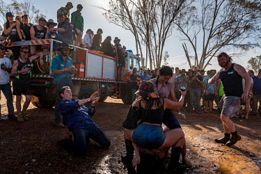 After the 'Wet T Shirt' competition, many of the men and some of the women start dancing, play fighting and wrestling in the mud at the Ariah Park Bachelor and Spinster ball.  Known to locals as sim...