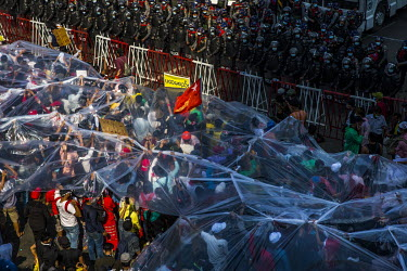 People use plastic sheets to protect themselves in case the security forces fire water canon at them, as tens of thousands of people gather on University Avenue Road to protest against the military di...