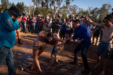 After the 'Wet T Shirt' competition, many of the men and some of the women start play fighting and wrestling in the mud at the Ariah Park Bachelor and Spinster ball. 'Rippy', a well known photographer...