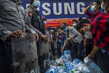Protestors offer water and food to the police as thousands gather to demonstrate in a show support for the NLD (National League for Democracy), Aung San Suu Kyi and democracy and to protest the 1 Febr...