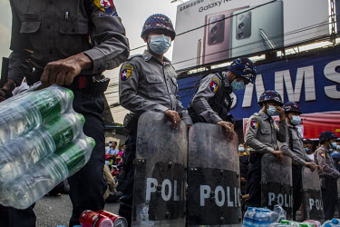 An officer collects water offered by protestors as riot police officers form a blockade in response to protestors, including student activists and factory workers, marching in a show support for the N...