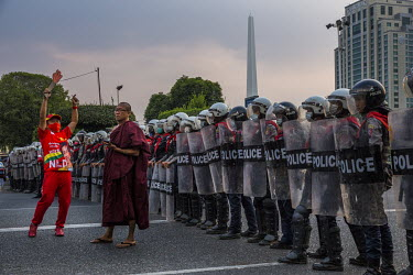 A Buddhist monk and a man dressed in NLD branded outfit stand in front of a line of riot police guarding Yangon's city hall where thousands of protestors have gathered to protest the military coup.