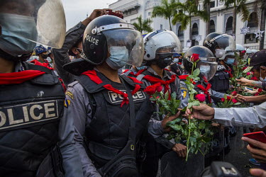 Protestors offer roses to riot police guarding Yangon's city hall where thousands of people have gathered to voice their opposition to the military coup.