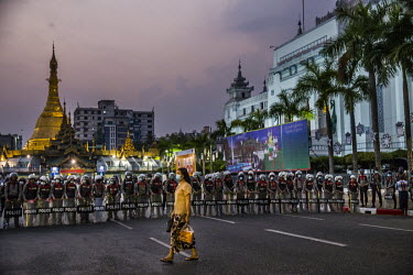 A woman walks past a line of riot police on guard in front of the Sule pagoda in the centre of Yangon.