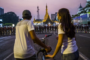 A couple wheel a bicycle past a line of riot police on guard in front of the Sule pagoda in the centre of Yangon.