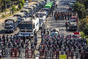 Riot police and soldiers gather behind barricades on University Avenue Road where a huge crowds has gathered to protest against the military dictatorship and demand the release of Aung San Suu Kyi and...