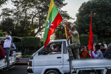 Pro-military supporters, including Buddhist monks, wave flags as dozens of trucks rally around Yangon, a day after the military seized power in a coup.