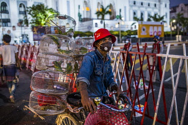 A vendor selling caged birds-to-free and wearing an NLD (National League for Democracy) hat, passes a police blockade in the square in front of city hall which has been guarded by soldiers since the m...
