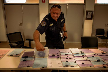 Paul Jones, sergeant at the Wadeye Police Station, looks through a selection of court documents representing individual cases, 90 of which are sheduled to be held at a 'bush court' during the followin...