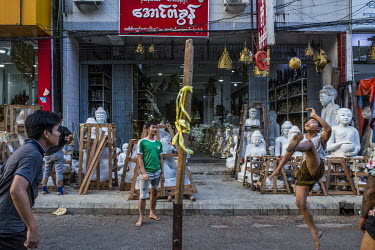 Workers play foot volleyball (takraw) on the street in front of a shop that sells Buddhist statues carved from marble.