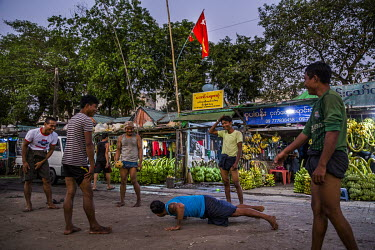 After work, labourers play sports at a banana market where an National League for Democracy (NLD) flag is displayed over the stalls.