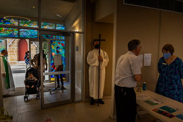 Rod Bower (left) greets Churchgoers at the entrance of the Anglican Parish of Gosford where they must sign in with the government COVID app.   Millions of people have viewed online Rod Bower's stateme...