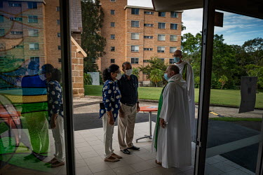 Rod Bower (2nd from right) greets Churchgoers at the entrance of the Anglican Parish of Gosford where they must sign in with the government COVID app.   Millions of people have viewed online Rod Bower...