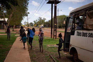 People alight from a council bus that serves the satellite communities on the edges of Wadeye town, helping residents to shop, attend school and access services found in the town. Due to tensions betw...