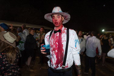 A man covered in red food dye walks toward the stage at the Ariah Park Bachelor and Spinster ball. Although food colouring is technically banned at the ball (security guards search patrons as they ent...
