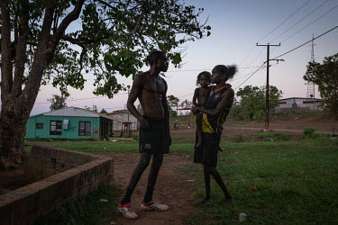 A couple with their child outside their home. Wadeye residents spend a lot of time outside their homes, cooking and playing as temperatures inside can become very hot and access to air-conditioning is...