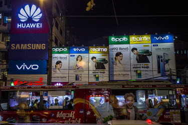 Illuminated advertisements above a parade of shops selling mostly Chinese brands of mobile phones and accessories.