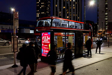 People board a bus at a stop in Elephant and Castle, during the 2021 COVID-19 lockdown. A digital display poster on the bus stop carryies a campaign advertisement for the National Lottery.