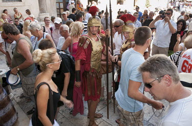Actors playing the Roman soldiers stare at a young female tourist visiting the Roman Palace.