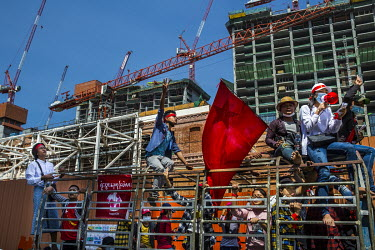A group of protestors singing anti-military songs and dancing on a truck pass the construction site of a shopping mall and hotels where work is currently suspended.