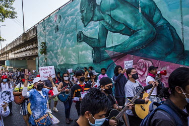 Guitar playing protestors march along a street while demonstrating in support of democracy, Aung San Suu Kyi and the National League for Democracy (NLD) and to protest the 1 February 2021 military cou...