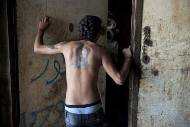 A man in the Shia district of Ghobeyreh with a tattoo of the fourth Caliph, Ali, on his back.