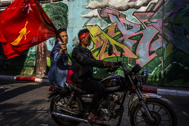 A woman flies the National League for Democracy (NLD) flag as she rides pillion on a motorcycle during demonstrations in support of democracy, Aung San Suu Kyi and the NLD, and to protest the 1 Februa...
