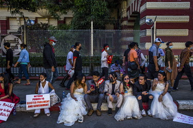 A group of artists wearing bridal wear costumes and holding protest placards sit in front of a government office building during demonstrations in support of democracy, Aung San Suu Kyi and the NLD, a...