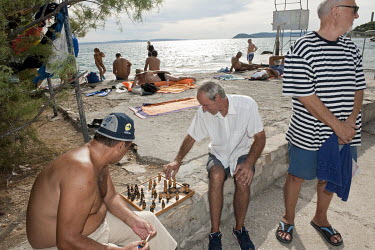 two men play a game of chess on a wall beside Bacvice city beach.