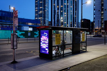 Travellers at a bus stop in Elephant and Castle, during the 2021 COVID-19 lockdown, where a digital display carries an advertisement for a domestic energy supplier.