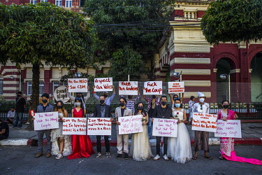 A group of artists wearing bridal wear costumes and holding protest placards in front of a government office building during demonstrations in support of democracy, Aung San Suu Kyi and the NLD, and t...