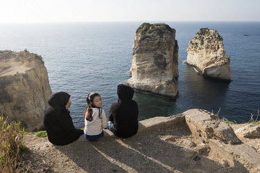 Syrian refugees near Pigeon Rock, natural rock stacks in the sea off the Corniche.