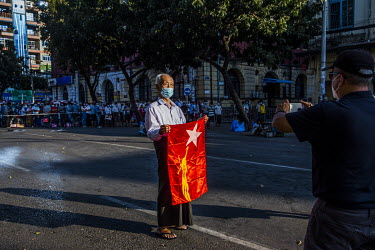 An elderly man holding a NLD (National League for Democracy) flag gets his picture taken by his son during demonstrations in support of democracy, Aung San Suu Kyi and the NLD, and to protest the 1 Fe...