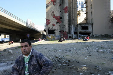 Syrian refugees gather near a building marked with shrapnel damage from the civil war.