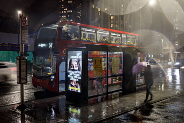 A bus at a stop in Elephant and Castle, during the 2021 COVID-19 lockdown, where a digital display carries a poster that is part of a campaign trying to promote compliance with coronavirus restriction...