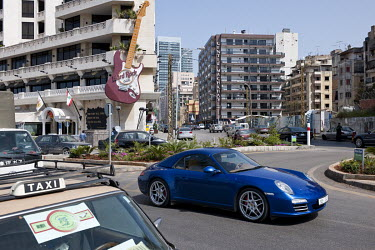 A blue Porche drives by the Hard Rock Cafe on the Corniche on the Mediterranean coast.
