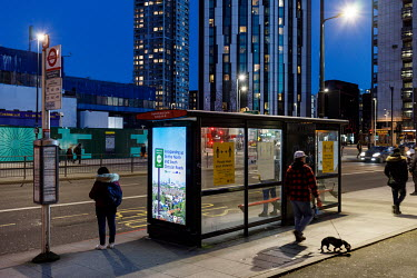 Travellers at a bus stop in Elephant and Castle, during the 2021 COVID-19 lockdown, where a digital display carries a poster warning that the ULEZ (ultra Low Emissions Zone) is to be widened.