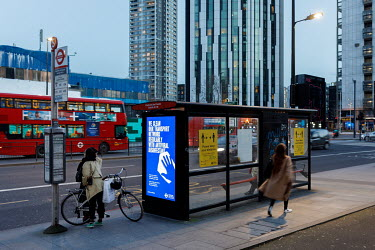 A bus at a stop in Elephant and Castle, during the 2021 COVID-19 lockdown, where a digital display carries a poster promoting Transport for London's coronavirus sanitation procedures.