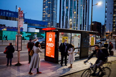 Travellers at a bus stop in Elephant and Castle, during the 2021 COVID-19 lockdown, where a digital display carries a poster that is part of a campaign trying to promote compliance with coronavirus re...