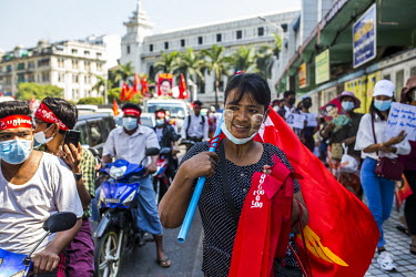 A street vendor selling clothing and flags in the red colours of the National League for Democracy (NLD) walks with protestors who have flooded the city centre to show their support for democracy, Aun...