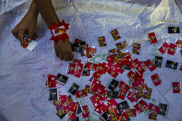 Young street vendors sells stickers with the picture of Aung San Suu Kyi during protests in the city centre in support of democracy, Aung San Suu Kyi and the National League for Democracy (NLD) and, a...