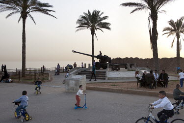Children play near a Howitzer monument on the Corniche, the pedestrian boulevard on the Mediterranean Sea front.