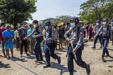 People watch as police retreat from a city neighbourhood after being forced out by the residents after they attempted to force Myanmar Railways staff, who joined the Civil Disobedience Movement (CDM),...