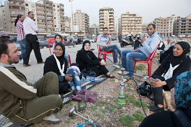 A family smoking waterpipes on the Mediterranean Sea front in the Al-Mina district.
