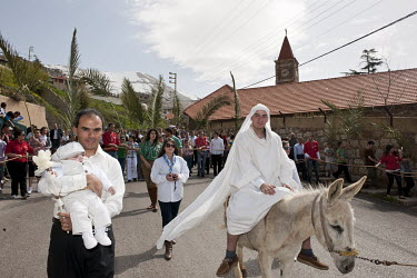 A man representing Jesus rides a donkey during a Maronite Christian Palm Sunday Easter procession.