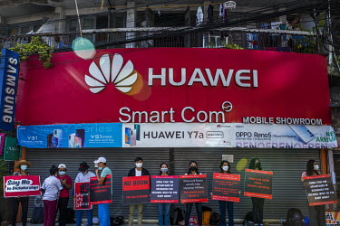 Protestors stand in front of a Huawei mobile phone shop holding placards include ones accusing Russia and China of complicity in the military coup.