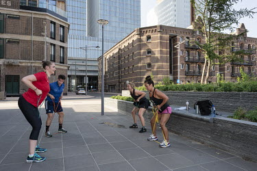 Office workers take part in a fitness class outside their workplace.