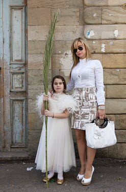 Maronite Christians Theresia and her daughter Magdalena gather on the steps of the Saint Saba Cathedral on Palm Sunday during Easter.